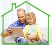 family, parenthood, technology and people concept - happy father and daughter with tablet pc computer at home behind green house symbol