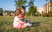 Baby girl and child playing sitting on a grass park