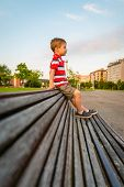 Boy sitting on the top of bench park relaxing