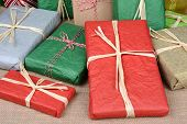 Closeup of a large group of wrapped Christmas presents on a burlap surface. A variety of presents wrapped with tissue paper and plain paper tied with string and raffia, Horizontal format.