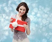 Attractive woman hands a present wrapped in red paper with white bow on blue light background