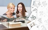 Two women looking at showcase with jewelry at jeweler's shop, sale labels background. Concept of wealth and luxurious life