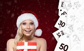 Pretty woman in Christmas cap hands present wrapped with red paper. Great discounts. Winter  sale