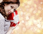 Young woman is satisfied with a christmas gift wrapped in red paper, gold background