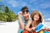 Couple packs up suitcase with clothing for honeymoon trip, tropical beach background. Concept of romantic vacations and lovely honeymoon