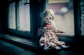Old porcelain doll on the stairs