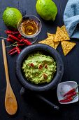 stock photo of nachos  - black stone bowl with fresh guacamole and nachos for dip - JPG