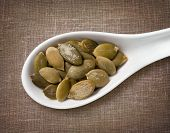 stock photo of spoon  - Peeled pumpkin seeds in white porcelain spoon  - JPG