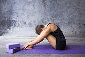 picture of yoga mat  - Woman sitting on her mat hiding her face between her legs - JPG