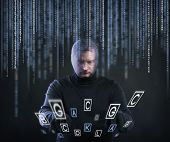 stock photo of stealing  - Thief in action stealing information with balaclava on his face - JPG