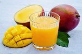 stock photo of mango  - mango juice and fresh mango on a blue background - JPG
