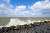 picture of dike  - Storm raging over a lake along a dike through Flevoland in spring - JPG