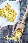 stock photo of millet  - raw millet in wooden spoon and on a table - JPG