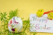 stock photo of decoupage  - Hand painted decoupage Easter egg on a handmade paper plate with a Happy Easter card and two yellow chickens  - JPG