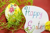stock photo of decoupage  - Hand painted decoupage Easter egg on red surface with a Happy Easter card and two yellow chickens  - JPG