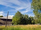 stock photo of backwoods  - Old wooden house in the village against a beautiful blue sky - JPG