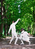 stock photo of rapier  - Two rapier fencers women fencing on park path - JPG