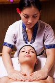 picture of therapist massage  - Confident Thai massage therapist massaging beautiful young woman lying on massage table and keeping eyes closed