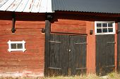 stock photo of red barn  - Sunlit old red barn wall with black doors and small windows - JPG