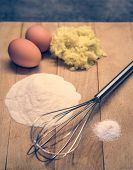 picture of raw materials  - Eggs flour and other raw materials on a wooden board  - JPG