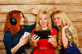 image of three sisters  - Three sisters blond and red listening to music on headphones - JPG