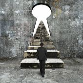stock photo of keyhole  - Man climbing old concrete stairs toward keyhole on concrete wall with blank white view - JPG