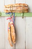 picture of hook  - Artisan French baguette breads wrapped with ribbons hanging on a vintage clothes hook - JPG