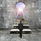 image of keyhole  - Man climbing old concrete stairs toward keyhole on concrete wall with view of sky clouds sun - JPG
