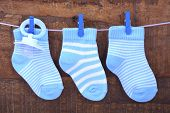 stock photo of pegging  - Its a Boy Blue Baby Socks and dummy pacifier hanging from pegs on a line against rustic dark wood background - JPG