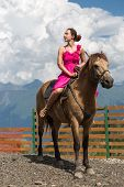 stock photo of mountain chain  - woman in evening dress on horseback in the mountains - JPG