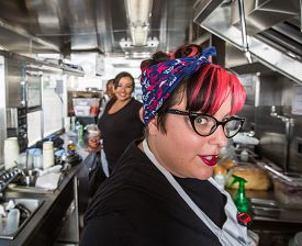 pic of food truck  - Female chef with pink hair working on food truck - JPG