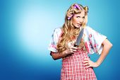Portrait of a pretty girl with curlers in her hair holding a knife. Over grey background.