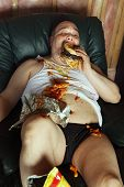 stock photo of couch potato  - Photo of a fat couch potato eating a huge hamburger and watching television - JPG