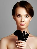 Постер, плакат: Beautiful Young Woman Applying Foundation On Her Face With A Make Up Brush Isolated On Gray Backgrou