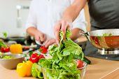 Mann und Frau in der Küche à ¢?? Sie Vorbereitung der Gemüse und Salat für Mittag- oder Abendessen