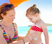 daughter and mother in beach with sunscreen in bikini
