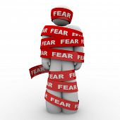picture of scared  - A man is wrapped in red tape reading fear representing the paralysis of being afraid and unable to move or act in the face of danger or something that scares or induces fright - JPG