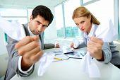 Retrato de empleados enojados con los papeles en manos mirando a cámara estrictamente