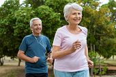 Senior couple running outside at park. Elderly man and old woman jogging together. Retired man and a poster