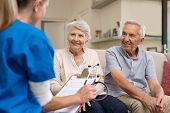 Nurse during home visit with senior couple. Doctor holding clipboard and stethoscope in conversation poster