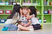 Two Girl Kids Whisper Secret At Ear Of Boy In Library At Kindergarten Preschool,fun And Happy Childr poster