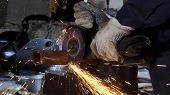Male Hand Cuts Off Pieces Of Water Pipe With Angle Grinder. Cutting Of A Steel With Splashes Of Spar poster