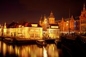 City scenic from Amsterdam with the central station at night in the Netherlands