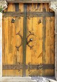 Antique Massive Wooden Doors With Wrought Handles, Rivets And Crossbars Illuminated By Bright Sunshi poster