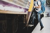 Young Asian Traveler With Backpack In The Railway, Traveler Holding And Stepping Up To A Train With  poster