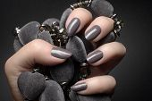 Female Hand With Gray Nails Is Holding A Gray Decoration On Dark Gray Background, Manicure And Nail  poster