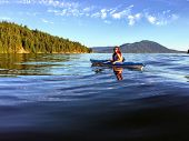 A Girl Enjoying Kayaking On The Beautiful And Calm Ocean Waters Of Howe Sound, Off Of Gambier Island poster
