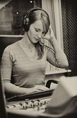 Portrait Of Female Dj Working In Front Of A Microphone On The Radio. Black And White