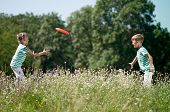 stock photo of frisbee  - Happy boy and little girl playing frisbee on a meadow in a sunny day - JPG