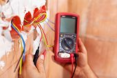 stock photo of  multimeter  - Electrician working with measuring instrument and wires  - JPG